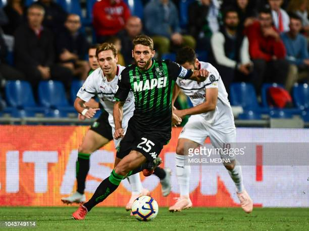 Sassuolo's forward Domenico Berardi fights for the ball with AC Milan's Argentine midfielder Lucas Biglia and AC Milan's Turkish midfielder Hakan...