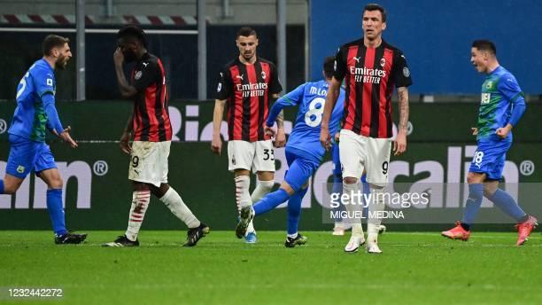 Sassuolo's Italian forward Giacomo Raspadori celebrates after scoring his second goal, as AC Milan's Croatrian forward Mario Mandzukic reacts during...