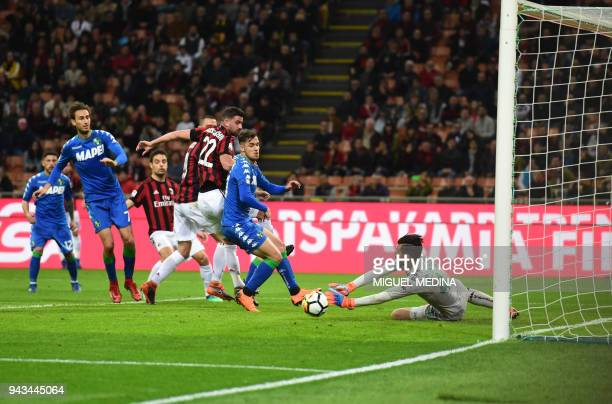 Sassuolo's Italian goalkeeper Andrea Consigli dives and stops a shot at goal during the Italian Serie A football match between AC Milan and Sassuolo...