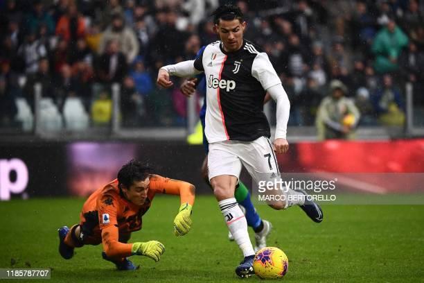 TOPSHOT Sassuolo's Italian goalkeeper Stefano Turati fights for the ball with Juventus' Portuguese forward Cristiano Ronaldo during the Italian Serie...