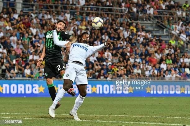 Sassuolo's midfielder Stefano Sensi and Inter Milan's Senegalese forward Keita Balde go for a header during the Italian Serie A football match...