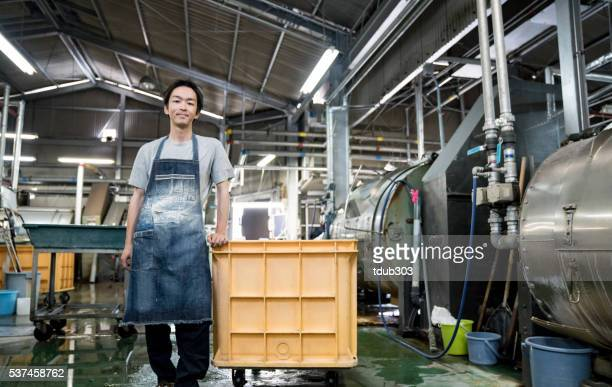 Sastisfied worker standing in a large garment washing facility