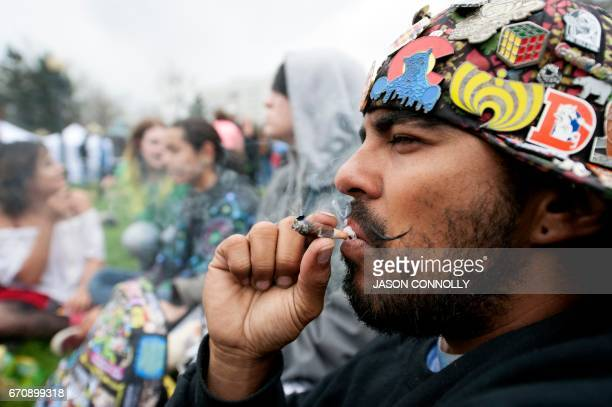 TOPSHOT Satan Valerio smokes a joint during the Denver 420 Rally at Civic Center Park in Denver Colorado on April 20 2017 The rally held annually is...