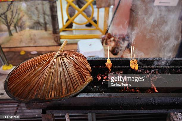 Satay barbeque with traditional cooking fan