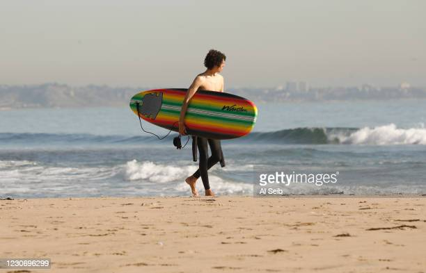 Satchel Freiberger from the San Fernando Valley enjoys the beautiful weather after a surfing session at Malibu Lagoon State Beach on Thursday as...