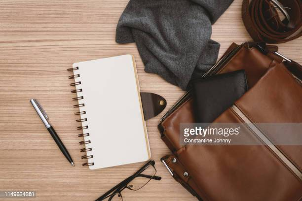 satchel men's bags and notebook on wooden desk - leather purse stock pictures, royalty-free photos & images