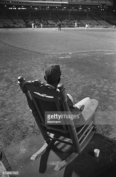 Satchel Paige, newly signed pitcher for the Kansas City Athletics, watches a Kansas City-Washington game from the comfort of a rocking chair in the...