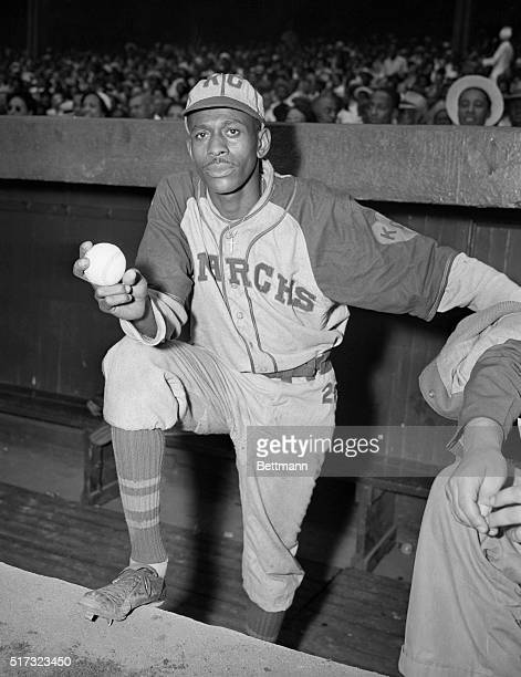 Satchel Paige, pitcher for the Negro League's Kansas City Monarchs, stands at the top of the dugout with baseball in hand. 1942.