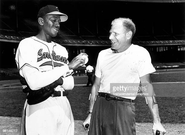 Satchel Paige shows Bill Veeck owner of the Cleveland Indians his new fastball grip before a night game at Municipal Stadium in Cleveland in 1949