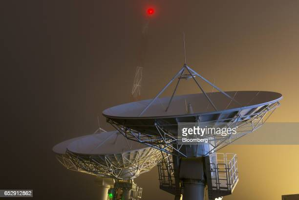 Satellite antennas stand illuminated at night at the Bolivian Space Agency Amachuma Ground Station in Achocalla La Paz Department Bolivia on...