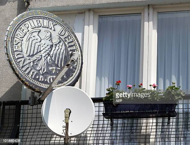 A satellite dish decorated with the image of a former Deutsche Mark coin by German artist Daniel Knipping hangs next to Geranium flowers on an...