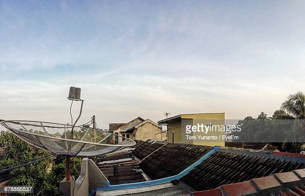 Satellite Dish On House Roof Against Sky