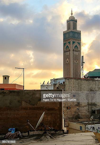 Satellite Dish On Roof With Minaret Against Cloudy Sky