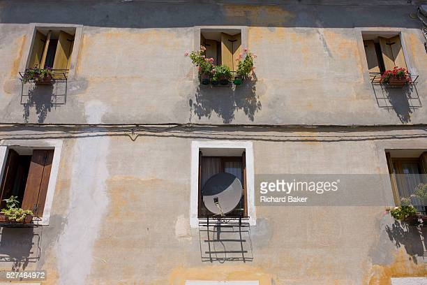A satellite dish takes up the space of an Italian home's window We look up at the series of windows of this old building in the centre of Bassano...