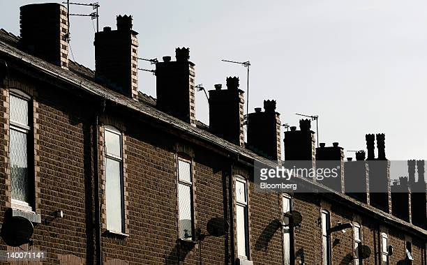 Satellite dishes hang from terraced housing in Irlam UK on Thursday Feb 23 2012 UK house prices held their value for a second month in February...