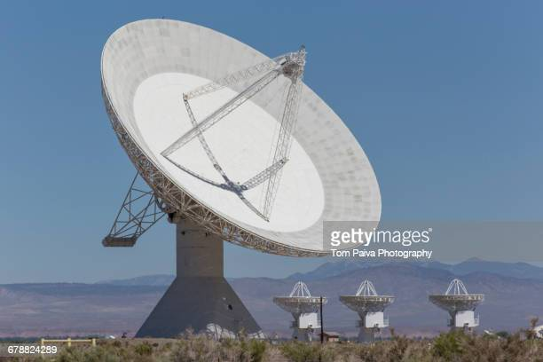 Satellite dishes in field near mountain range