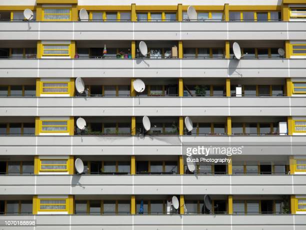 satellite dishes on balconies of residential building in the district of kreuzberg, berlin - kreuzberg stock photos and pictures