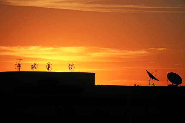 Satellite dishes on rooftop of a building at sunrise