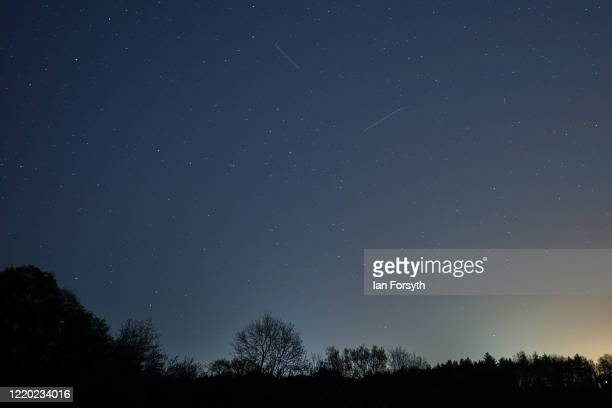 Satellite from a larger group of satellites called Starlink can be seen trailing across the night sky as another satellite heads towards it in the...