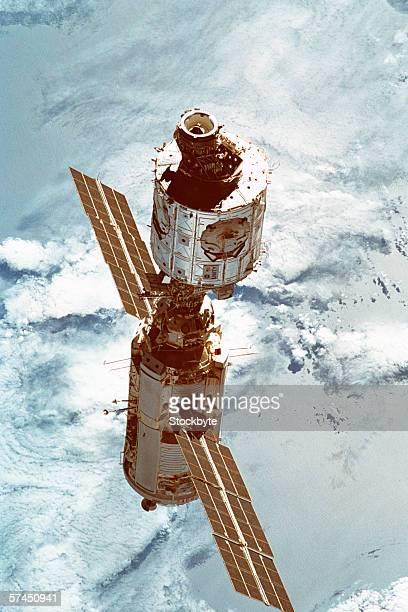 a satellite in orbit above earth - orbiting stock-fotos und bilder