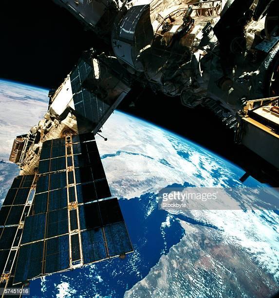 a satellite orbiting above the earth - orbiting stock-fotos und bilder