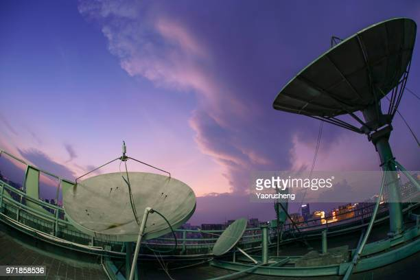 Satellite television dish on the building over city bay at twilight sunset,beautiful cloud and monster shape of cloud due to the typhoon coming