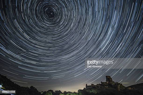 Satellites planes and comets transit across the night sky under stars that appear to rotate above Corfe Castle on August 12 2016 in Corfe Castle...