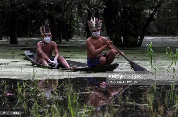 Sateremawe indigenous men navigate the Ariau river during the COVID19 novel coronavirus pandemic at the SahuApe community 80 km of Manaus Amazonas...