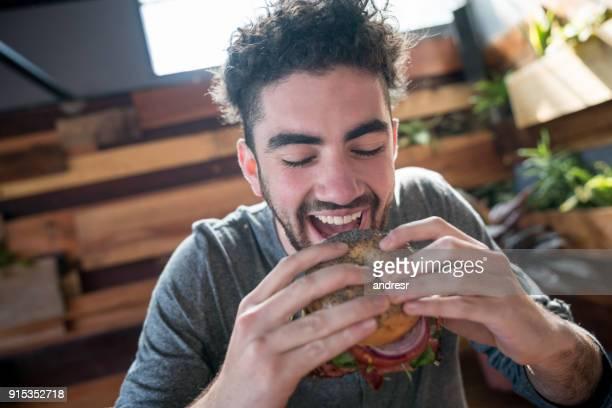 moch junger mann mit geschlossenen augen einen burger zum anbeißen - servierfertig stock-fotos und bilder