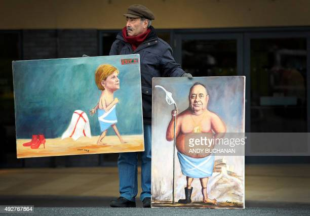 Satirical artist Kaya Mar stands with paintings of Scotland's First Minister and leader of the Scottish National Party Nicola Sturgeon and former...