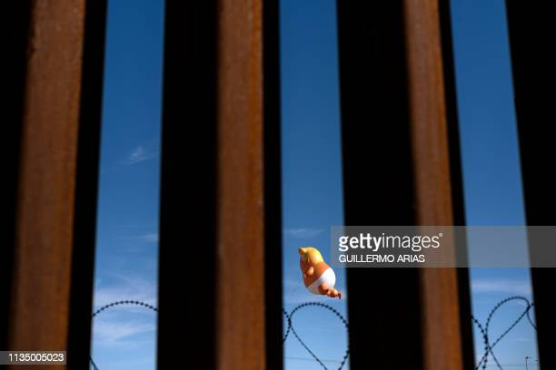 TOPSHOT A satirical balloon of a baby US President Donald Trump is seen through the USMexico border fence during a demonstration against him prior to...