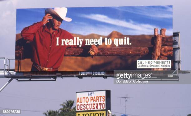 A satirical billboard of the iconic Marlboro Man in March 1993 reads I really need to quit with the Marlboro Man on a cell phone in Los Angeles...