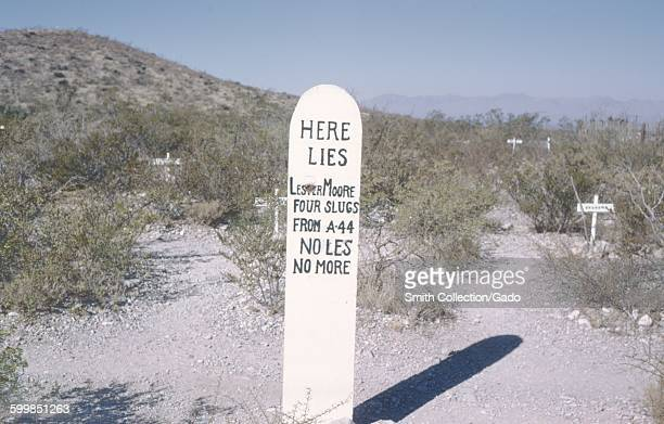 Satirical grave marker for Lester Moore, reading Lester Moore, Four Slugs from an A44, No Les No More, Tombstone, Arizona, 1966.