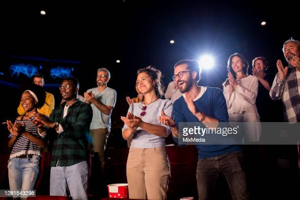 satisfied audience applauding at the end of a movie at the cinema - film festival stock pictures, royalty-free photos & images