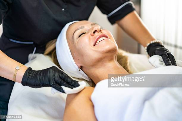 satisfied client lying on bed in beauty salon - medical procedure stock pictures, royalty-free photos & images