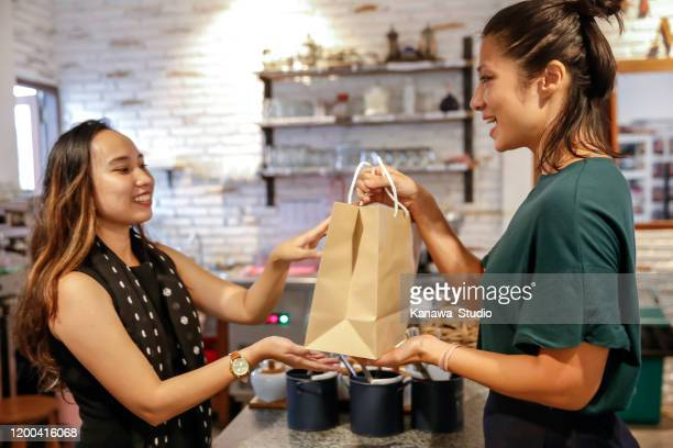 satisfied customer picking up food in paper bag - passing giving stock pictures, royalty-free photos & images
