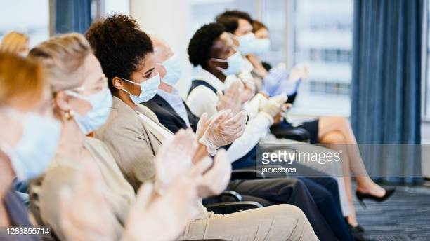 satisfied entrepreneurs in protective masks applauding at conference. new normal - attending stock pictures, royalty-free photos & images