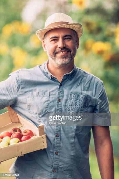 Satisfied Fruit Grower Holding A Crate Of Apple