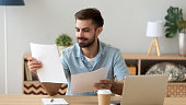 Satisfied man reading paper documents, working with laptop