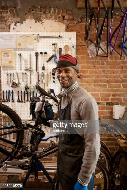 satisfied mechanic holding up bicycle - heshphoto - fotografias e filmes do acervo