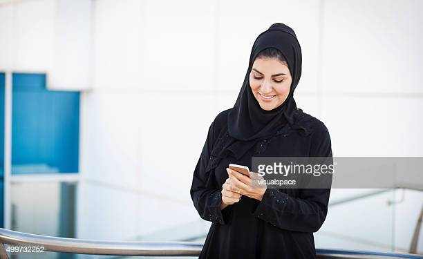 Satisfied Middle Eastern Businesswoman Using Phone Outside Office