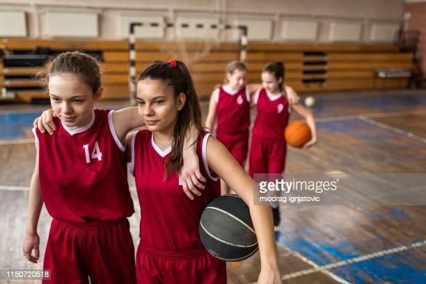 tevreden tiener meisjes verlaten basketbalveld - teamsport stockfoto's en -beelden