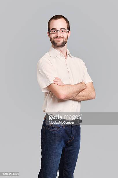 Satisfied young bearded man with arms crossed