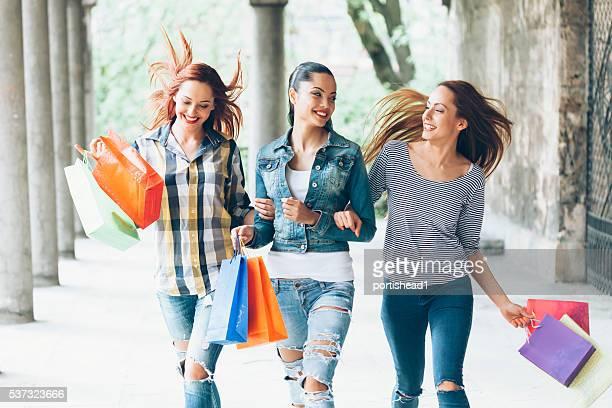 Zufriedene Junge Freunde halten bunte purcheses