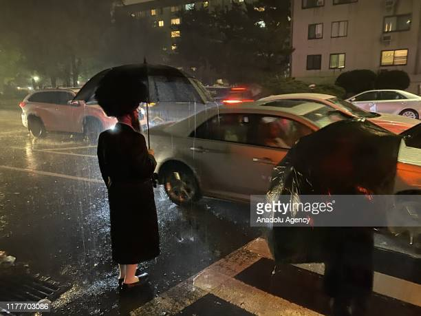 Satmar Jews stand in rain with umbrellas at a crosswalk as they make their way to celebrate the Sukkot, the Feast of the Tabernacles, in New York,...
