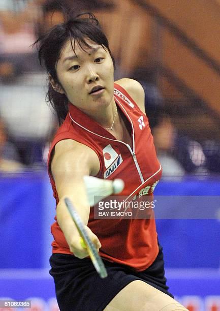 Satoko Suetsuna of Japan returns the shuttlecock to Lim Pek Siah of Malaysia during their woman's singles match at the Uber Cup badminton tournament...