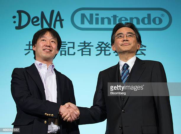 Satoru Iwata president of Nintendo Co right and Isao Moriyasu president and chief executive officer of DeNA Co shake hands during a joint news...