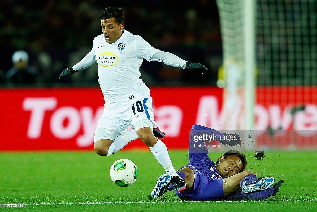 Satoru Yamagishi (R) of Sanfrecce Hiroshima challenges Luis Corrales of Auckland City during the FIFA Club World Cup match between Sanfrecce Hiroshima and Auckland City at International Stadium Yokohama on December 6, 2012 in Yokohama, Japan.