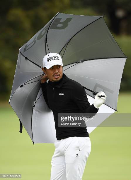 Satoshi Kodaira of Japan protects himself from the weather during day three of the 2018 World Cup of Golf at The Metropolitan on November 24 2018 in...
