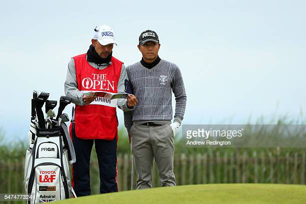 Satoshi Kodaira of Japan speaks with his caddies Tomo Hiro on the 1st green during the second round on day two of the 145th Open Championship at...